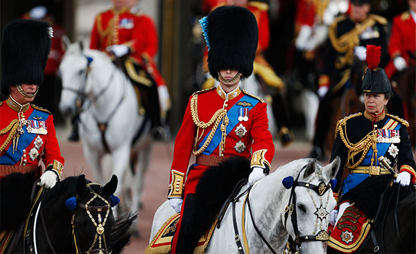 Britain's Prince Charles, left, Prince William, centre, and Princess Anne, right, ride their horses as they escort Queen Elizabeth II, to attend the Trooping the Colour parade, in central London, Saturday, June 14, 2014.