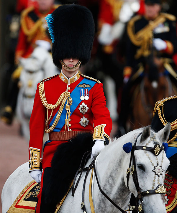 Britain's Prince William rides his horse as he escorts Queen Elizabeth II, as they leave Buckingham Palace to attend the Trooping the Colour parade, in central London, Saturday, June 14, 2014.