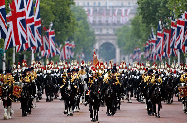 British soldiers ride their horses as the escort Queen Elizabeth II in a horse drawn carriagevas she returns to Buckingham Palace, during the Trooping The Colour parade, in central London, Saturday, June 14, 2014.